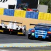 Porshe 911 RSR LM GTE Pro No. 77 gets passed into the corner by a faster LMP2 Car